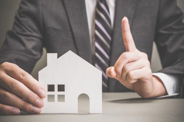 住宅模型と背広の男性
